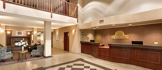 The spacious lobby with a fireplace, chairs and more at Days Inn in Thunder Bay North